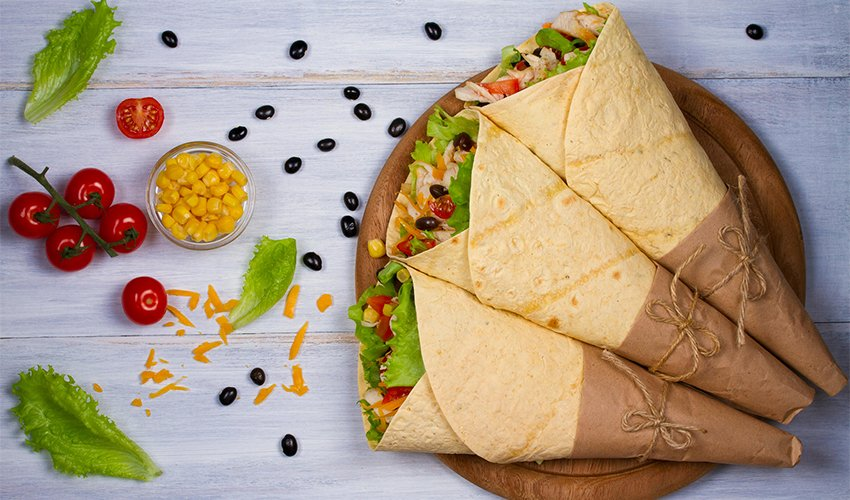 Wraps with chicken, tomatoes, lettuce, black beans, cheddar cheese and sweet corn