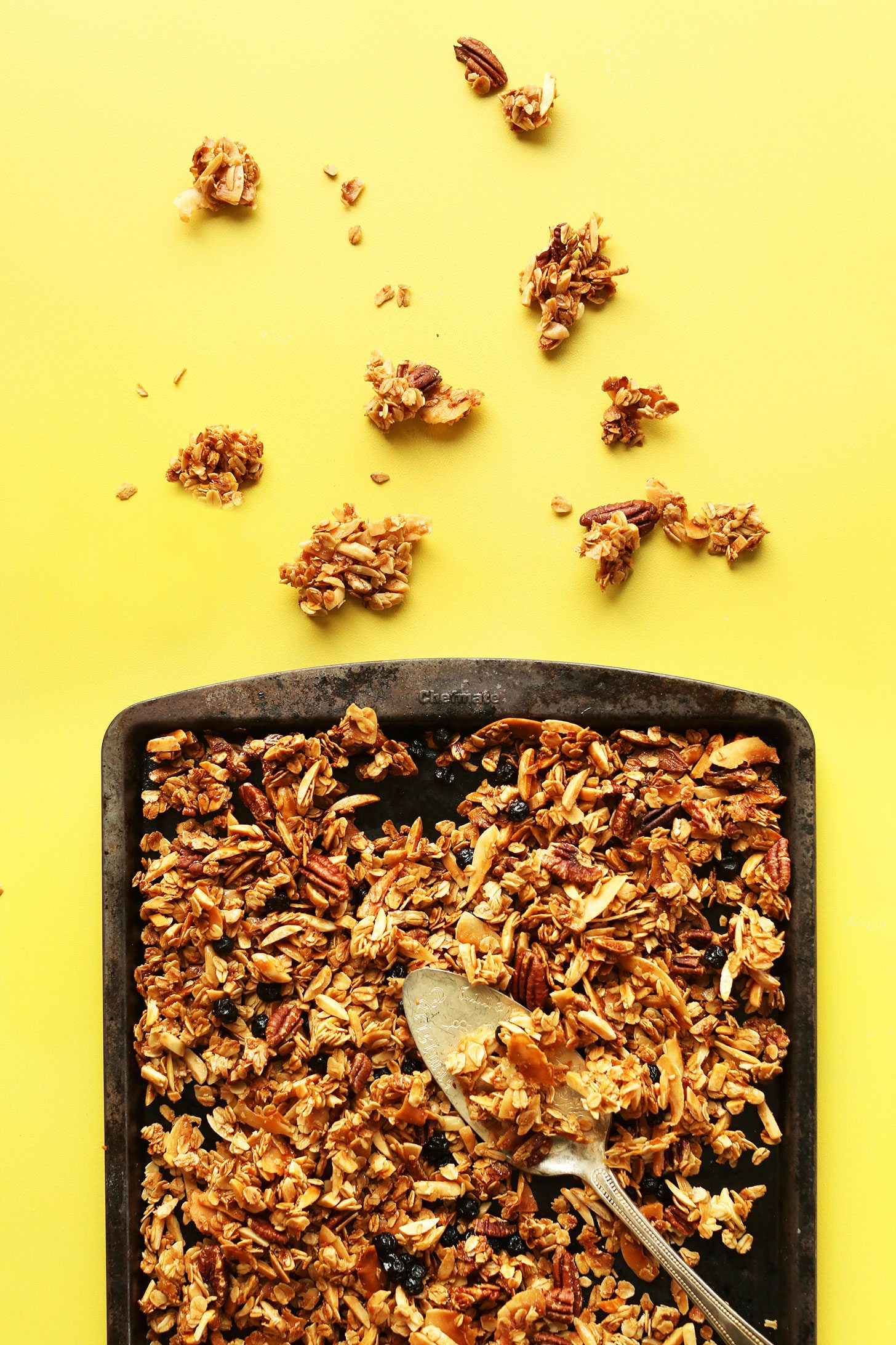Coconut granola in the baking pan on the yellow background