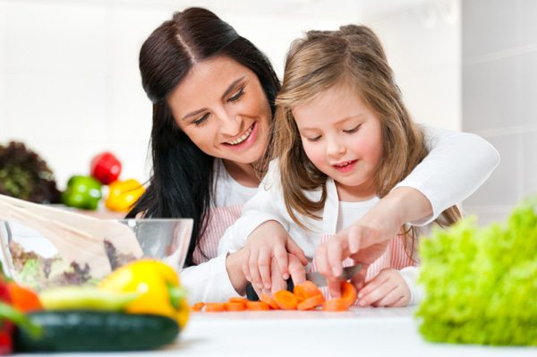 A mom and her daughter are cooking meals
