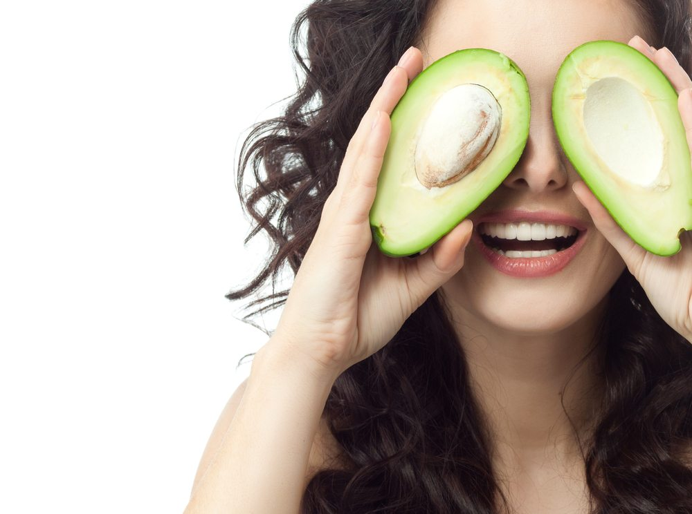 A woman holding an avocado in fron of her eyes