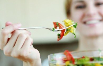 A woman eating a vegetable salad