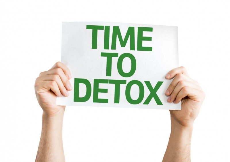 "A man holding a paper with words ""time to detox"""