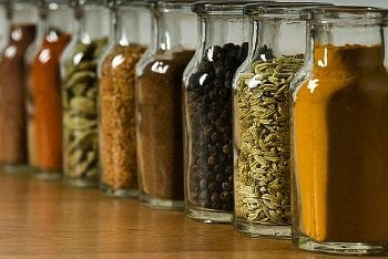 Different spices in glass jars on a table