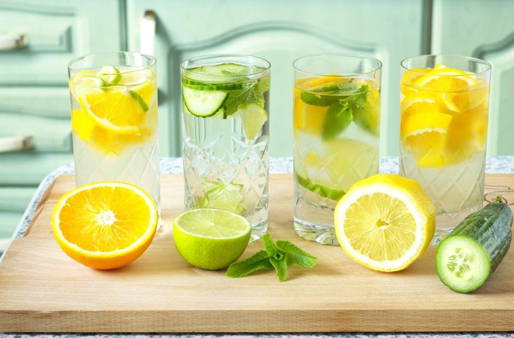 four glasses of water with lemons and liams