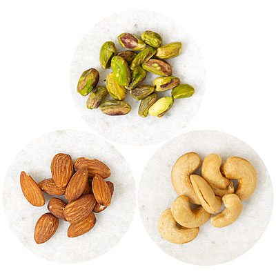 Аlmonds, cashews, pistachios are lying on small plates