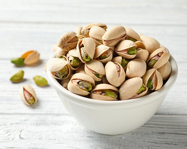 Roasted and salted pistachio nuts in bowl on wooden table, closeup