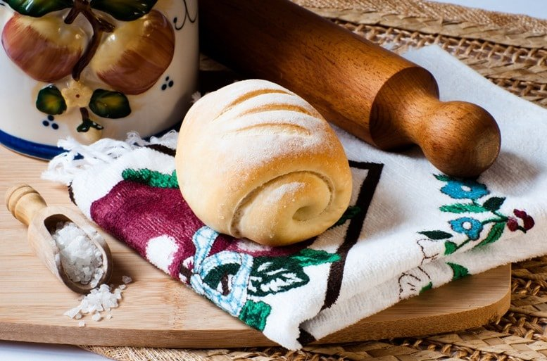 Kamut bread on a kitchen cloth displayed with a wooden spoon of salt a decorated jar and a rolling